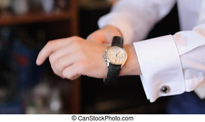 The man in the white shirt fixing watches. Close-up hands on interior background