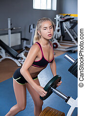 Girl in the gym - Girl putting weight plate on the bar