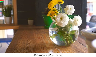 Beautiful flowers in a glass vase on a table in cafe