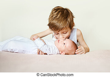 baby in white pajamas lying on his back. Older brother kisses