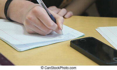 Schoolgirl writes text in exercise book on lesson - The...