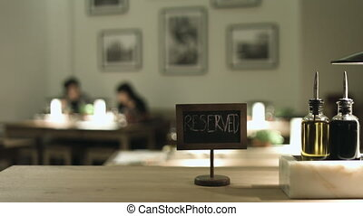 Table with a sign 'reserved' with a couple on the background