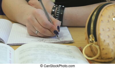 Student writes text in a exercise book using a pen - The...