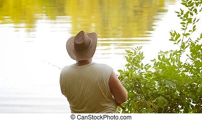 large man with hat fishing on a fishing rod, sport fishing...