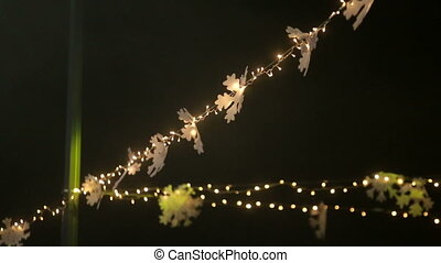 Blurred image of light bulbs outdoor on a wire, holiday concept