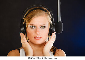 Woman singing to microphone wearing headphones in studio -...