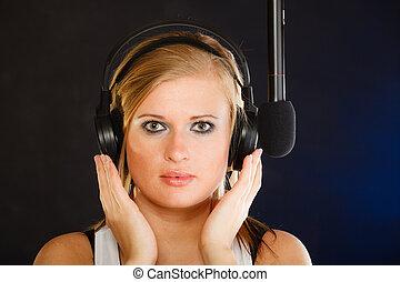 Woman singing to microphone wearing headphones in studio -...