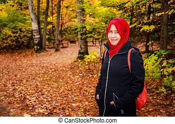 Muslim woman in North America during autumn with colorful...