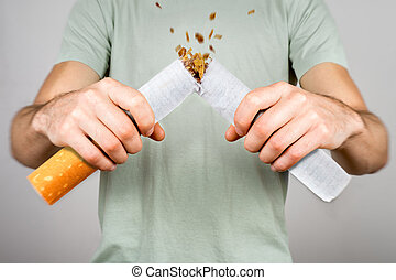 Quit smoking - male smoker breaking giant cigarette