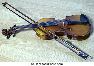 vintage violin with a bow lies on wooden bench