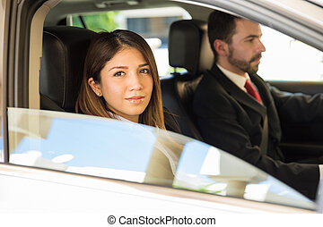Business couple driving a car