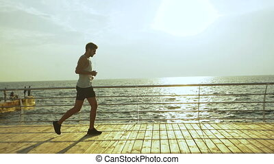 Young handsome active man running and taking a while to relax after long running distance.