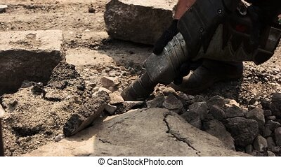 Worker with pneumatic hammer drill. Dirt and rocks. Work in...