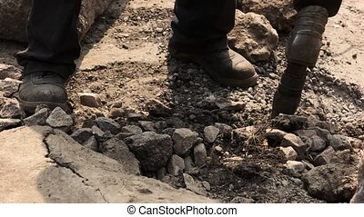 Worker holding pneumatic hammer drill. Dirt and small rocks....