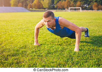 Fitness man doing push-ups on the grass.