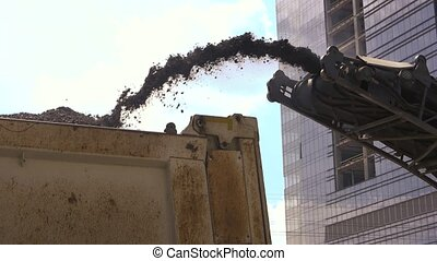 Pile of milled asphalt. Conveyor of cold planer. Building...