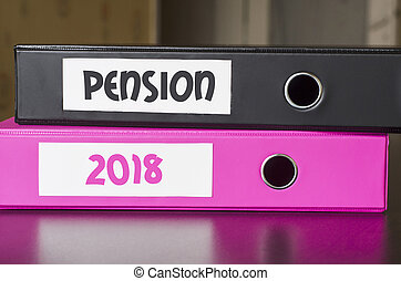 Bright office folders over dark background and pension 2018...