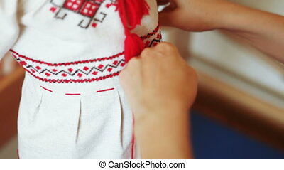 Dressing dress embroidered shirts - Mother helps daughter to...