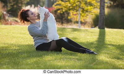 young lady with Maine Coon cat on the grass