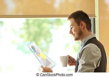 Business man reading growth statistics - Side view of a...