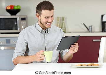 Man reading news in a tablet at breakfast - Happy man...