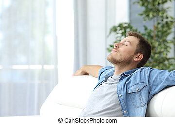 Man resting on a couch at home - Portrait of a casual tired...