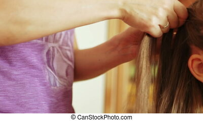Splicing at girl pigtails - Mother braiding daughter's...