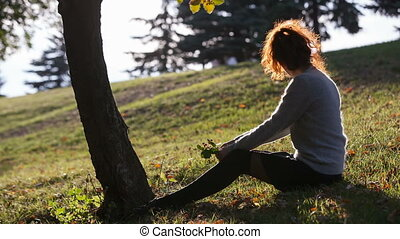 young lady seats on the grass as silhouette