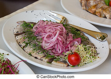 Herring fillets with onion on a dish with a fork