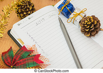 Notebook on a wooden table with new year goals 2017