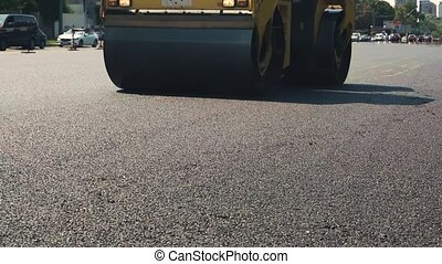 Road roller is moving. Traffic in the city. Planned repair...