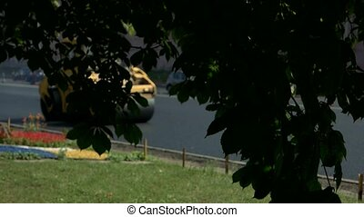 Yellow road roller in motion. Foliage of tree. Repair of...