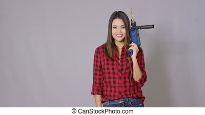 Capable young woman holding a power drill in her hand giving...