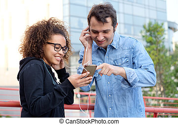 Two friends using mobile phone and listening to music in the street