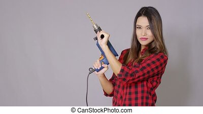 Capable attractive young woman holding a drill - Capable...