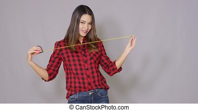 Female constructor worker with measure tape. She joking and...