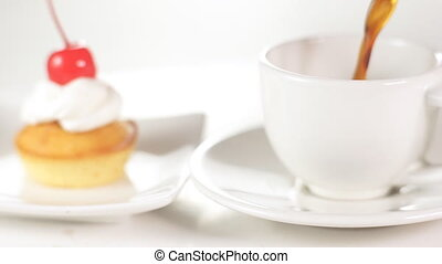 Poring a coffee into the white cup with cup cake on the...