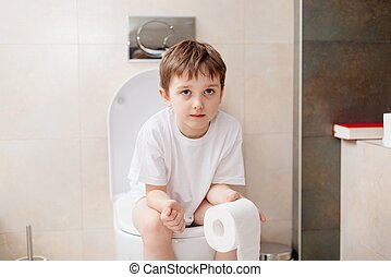 Little 7 years old boy sitting on toilet. Holding white...