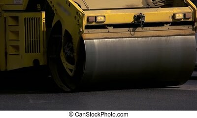 Drum roller on road. Dark asphalt surface. Tight schedule of...