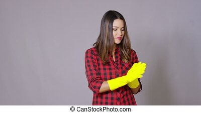 Attractive housewife holding up gloved hands in colorful...