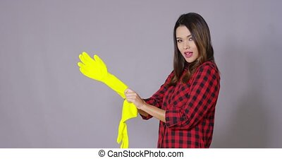 Young housewife putting on rubber gloves - Young housewife...