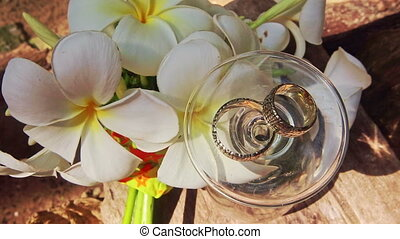 Turned over Wine Glass Wedding Rings on Top by White Flowers...