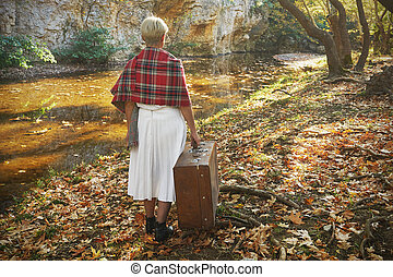 Lonely woman with a suitcase walking in the forest an autumn day.
