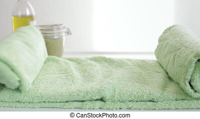 Applying moisturizing cream on dry foot skin on green towel