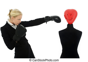 portrait of a young caucasian businesswoman with aggressive air wearing boxing gloves and punches a dummy