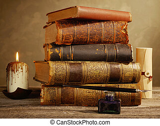 Ink pot, quill, candle and antique books