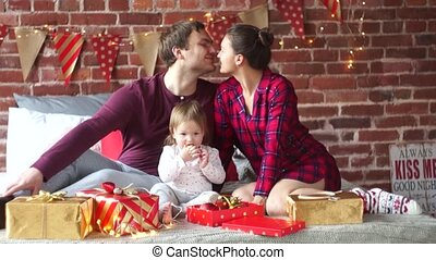 Young family gleefully congratulates each other Marry Christmas.