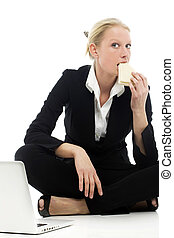 portrait of a young caucasian businesswoman eating sitting on the floor with laptop