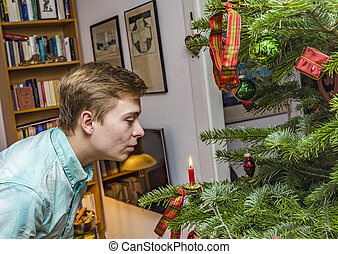 boy blows out the red candle at the christmas tree - boy...