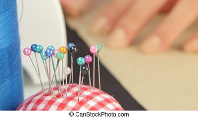 Pins for sewing. Close up - Pins for sewing, woman encircles...